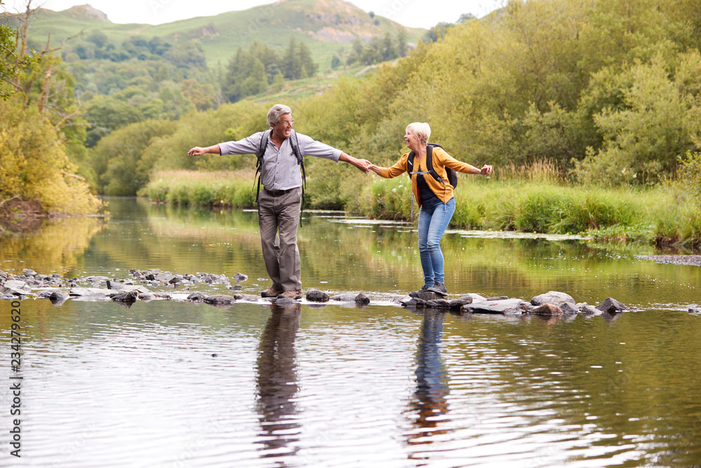 Fototapety, obrazy: Senior Couple Crossing River Whilst Hiking In UK Lake District