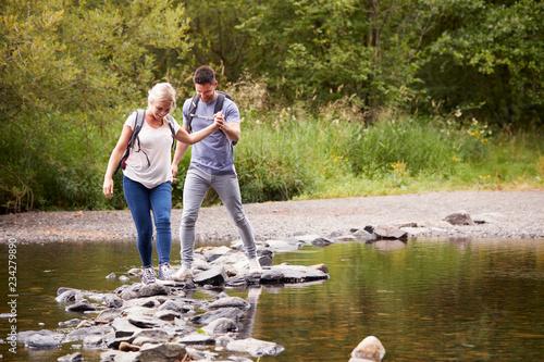 Fototapeta Couple Crossing River Whilst Hiking In UK Lake District