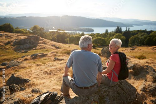 Fotografia  Senior Couple Resting At Top Of Hill On Hike Through Countryside In Lake Distric