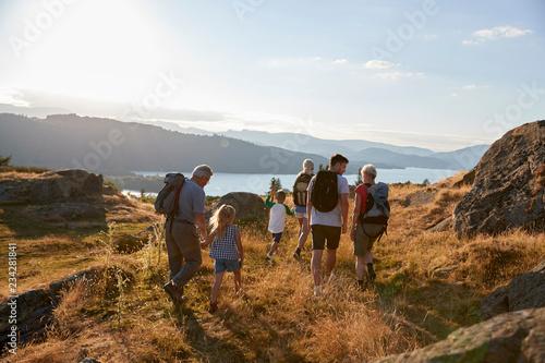 Obraz na płótnie Rear View Of Multi Generation Family Walking On Top Of Hill On Hike Through Coun