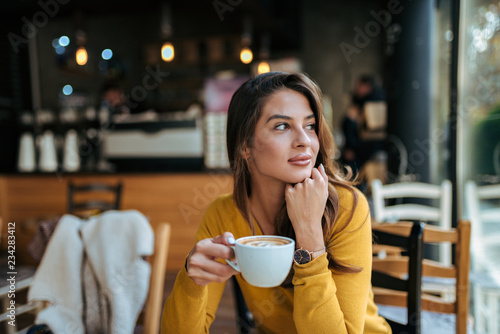 Fotografía Stylish young woman drinking coffee at the cafe, looking away.