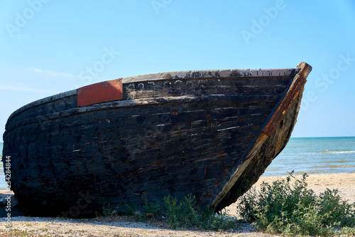 Old abandoned wooden fishing boat with rusted nails by the sea