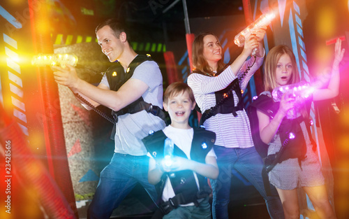 Kids and parents in beams during laser tag game - Buy this