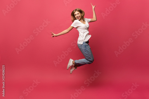 happiness, freedom, motion and people concept - smiling young woman jumping in a Canvas Print