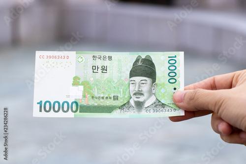 Fotomural  Man hold south korea banknote 10000 won on blurred background