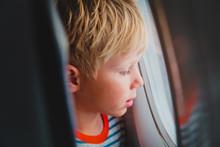 Little Boy Travel By Plane Looking Through Window