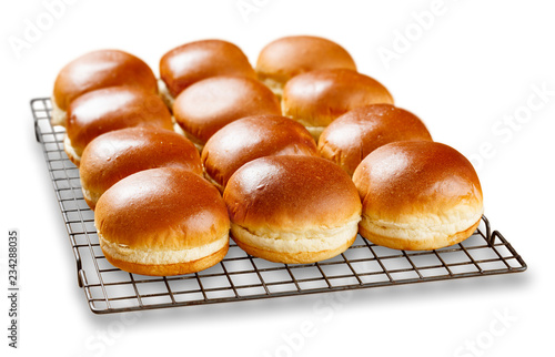 Brioch buns cooling on a wire tray.
