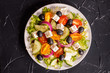 Greek salad with fresh vegetables, feta cheese and black olives on a dark stone slate background. Top view. Free space for your text.