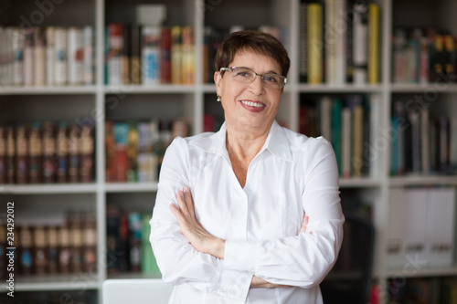 Fotografie, Obraz Portrait of  senior businesswoman wearing glasses head shot in a white shirt, cr