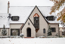 Charming White Painted Brick Cottage With Copper Accents During Snowfall With Autumn Leaves Still On Trees