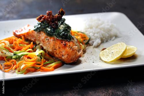Fototapeta Łosoś na warzywnym spaghetti. Ryba z grilla w sosie  śmietanowo szpinakowym na warzywnym spaghetti  z marchewki i cukini obraz