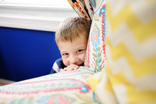 Lovely Little Boy In Striped Jumper Playing Hide And Seek At Home