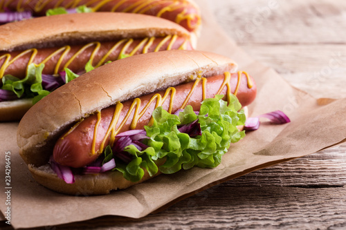Hot dog with yellow mustard, lettuce and onions