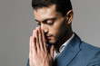 Image of adult arabic businessman 30s in formal suit holding palms together for pray, isolated over gray background