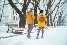 Couple Walking By Snowed City Park Talking Socializing. Romantic Date In Winter Time