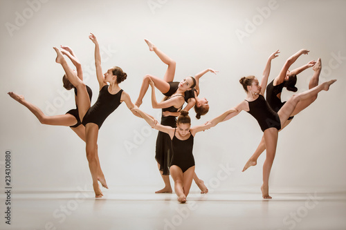 The group of modern ballet dancers dancing on gray studio background