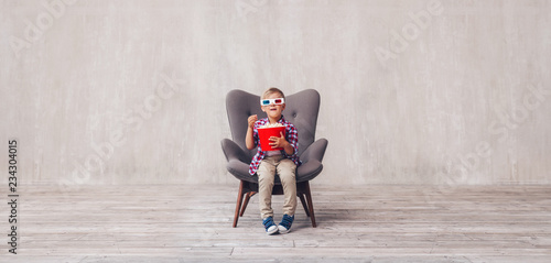 Little boy in 3d glasses with popcorn