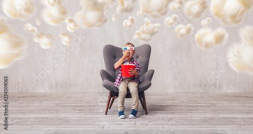 Little child in 3d glasses eating popcorn