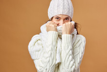 Nice Girl Dressed In White Knitted Sweater And Hat Closes Her Face With White Scarf On A Beige Background In The Studio
