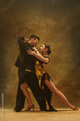 The young dance ballroom couple in gold dress dancing in sensual pose on studio background Wallpaper Mural