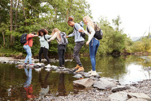 Multi Ethnic Group Of Five Young Adult Friends Hold Hands Balancing On Rocks To Cross A Stream During A Hike