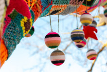 Knitted Baubles With Patchwork Tree Covering And Christmas Stars And Blue Sky In The Background