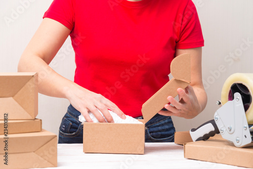 Fotografia Woman packing cardboard boxes , picking and puttind products
