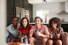 Four Young Adult Friends Watching Sports On TV At Home