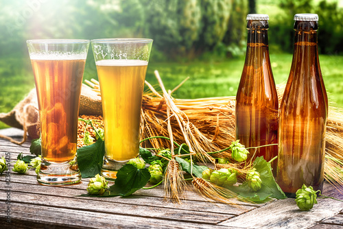 Tuinposter Bier / Cider Glasses with fresh cold beer in rustic setting
