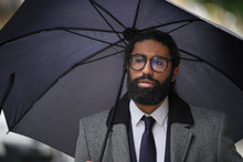 Portrait Of Businessman Using Umbrella On A Rainy Day