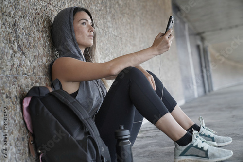 obraz dibond Woman in sportswear sitting down in a tunnel with her cellphone