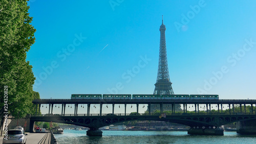 Photo Stands Paris Paris, France - circa May, 2017: Traffic in Paris with Eiffel Tower and Bir Hakeim bridge over Seine River, vehicles on road and metro train over bridge