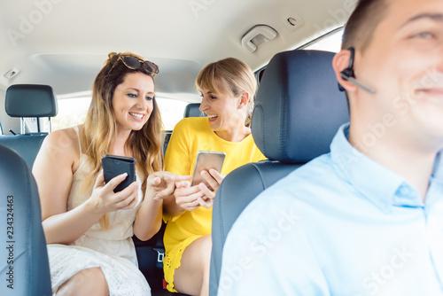 Cuadros en Lienzo Freundinnen nutzen ihre Telefone auf dem Rücksitz von Taxi