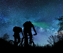 Couple Ride Bicycles At Night Under The Milky Way