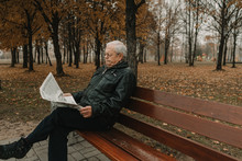 Elderly Man Reading Newspaper In Park