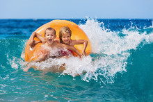 Happy Kids Have Fun In Sea Surf On Beach. Joyful Couple Of Children On Inflatable Ring Ride On Breaking Wave. Travel Lifestyle, Swimming Activities In Family Summer Camp. Vacations On Tropical Island