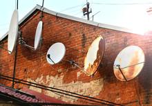 Old Weathered Satellite Dish On A Brick Wall. Telecommunication Concept.
