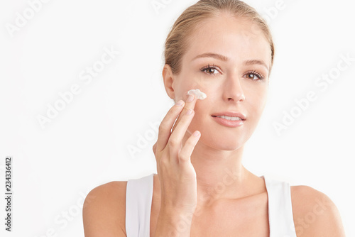 Fotografiet Young woman applying face cream against white isolated background