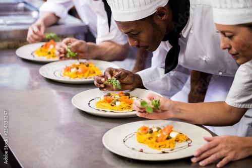 Chef garnishing food on plates