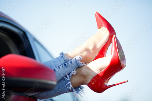 Carta da parati Image of girl's legs in red shoes sticking out of red car window