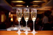 Glasses With Champagne On The Bar Counter In A Restaurant Against A Dark Background.