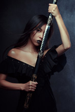Portrait Of A Beautiful Girl Of Asian Appearance With A Canana In Her Hands Against A Dark Background.