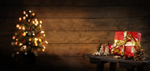 Red Gift Box And Christmas Decoration On An Old Stool, Blurry Tree With Lights In The Background Against A Rustic Wooden Wall, Copy Space, Panoramic Format