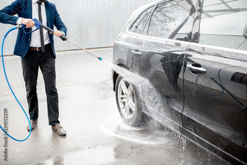 Businessman Dressed In The Suit Washing His Luxury Car With Washing