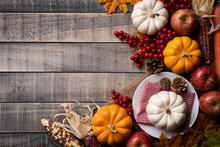 Top View Of  Autumn Maple Leaves With Pumpkin, Apple, Corn And Red Berries On Old Wooden Background. Thanksgiving Day Concept.