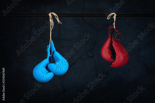 Valokuvatapetti blue and red fighting gloves hang on a cordlike rope on a rod against the old wa