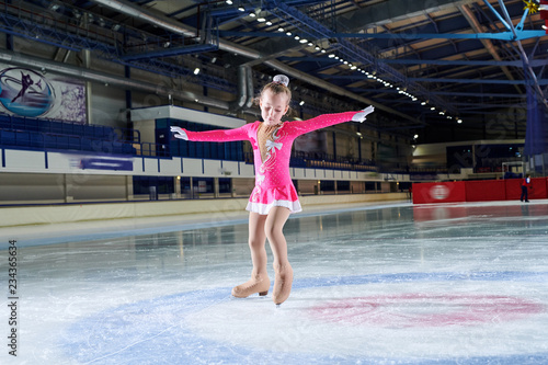 Full length portrait of talented little girl figure skating in indoor rink posing in spotlight, copy space