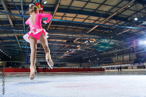 Back view portrait of teenage girl jumping up doing figure skating move during figure skating performance in spotlight, copy space