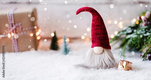 Frohe Weihnachten - Kleiner Wichtel zwischen Geschenken, Schnee und weihnachtlicher Dekoration im Winter