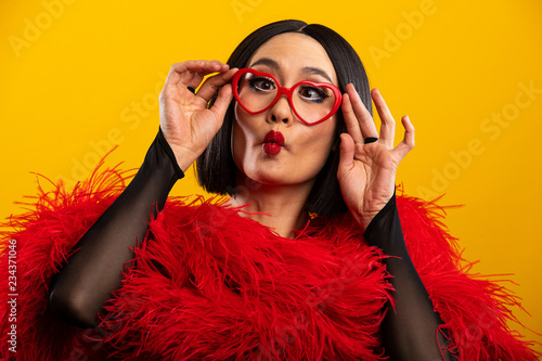 Fotografie, Obraz  Asian woman puckering lips wearing red feather boa and heart shaped glasses
